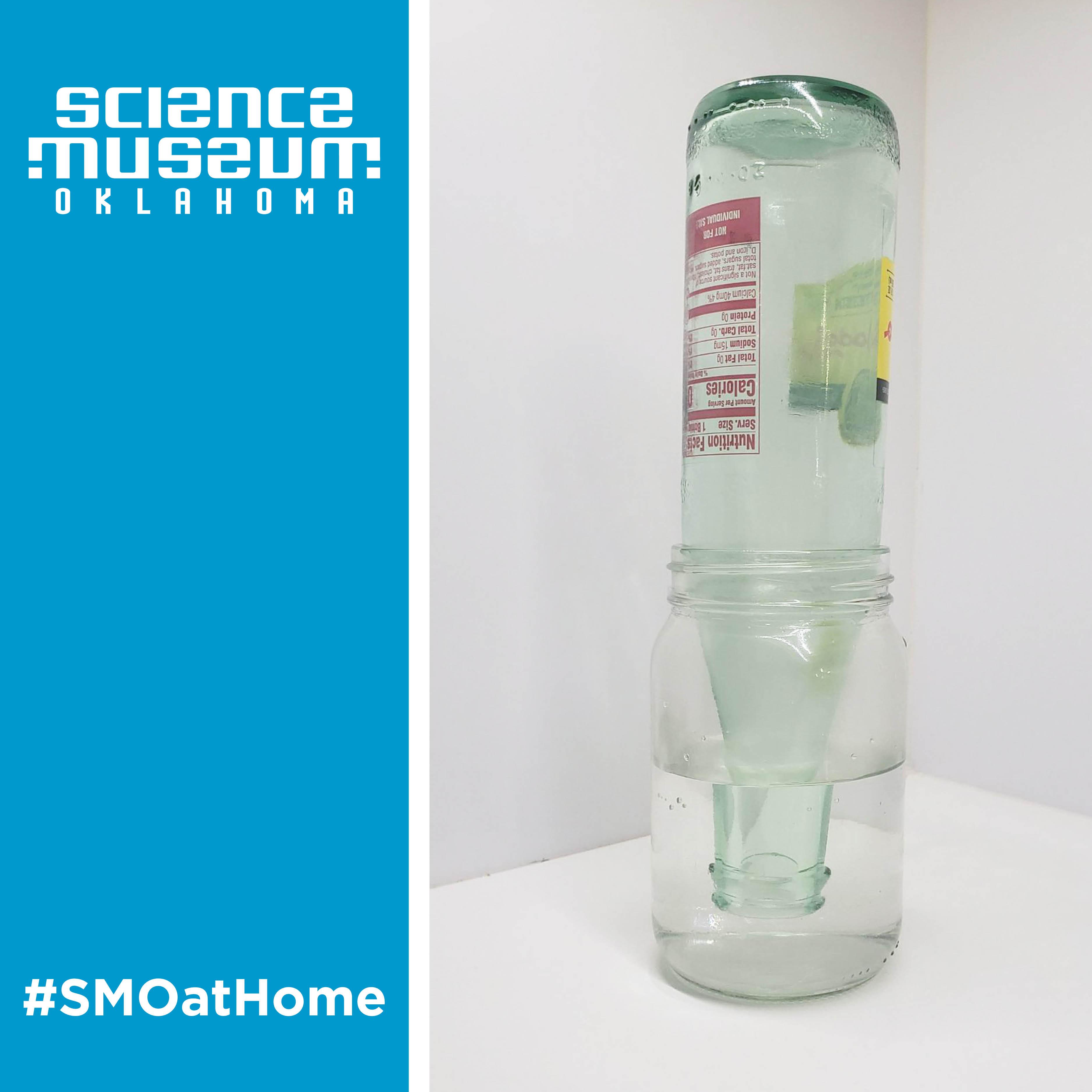 Photo of a glass bottle upside down in a mason jar. The jar has water in it.